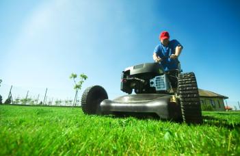 un homme qui tond sa pelouse