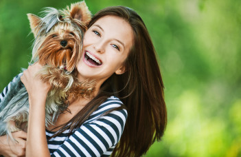 Femme qui tient un chien dans ces bras